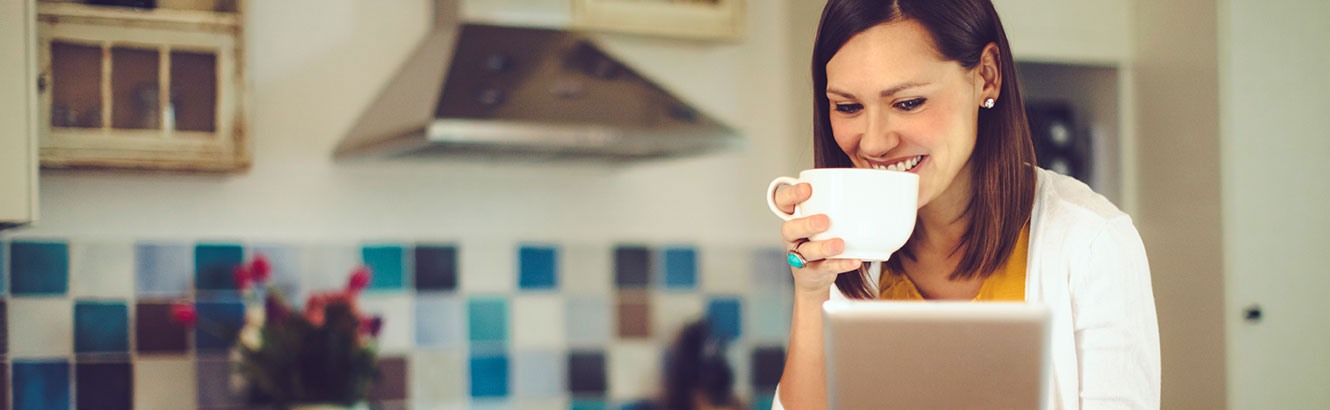 Young woman using tablet while drinking coffee